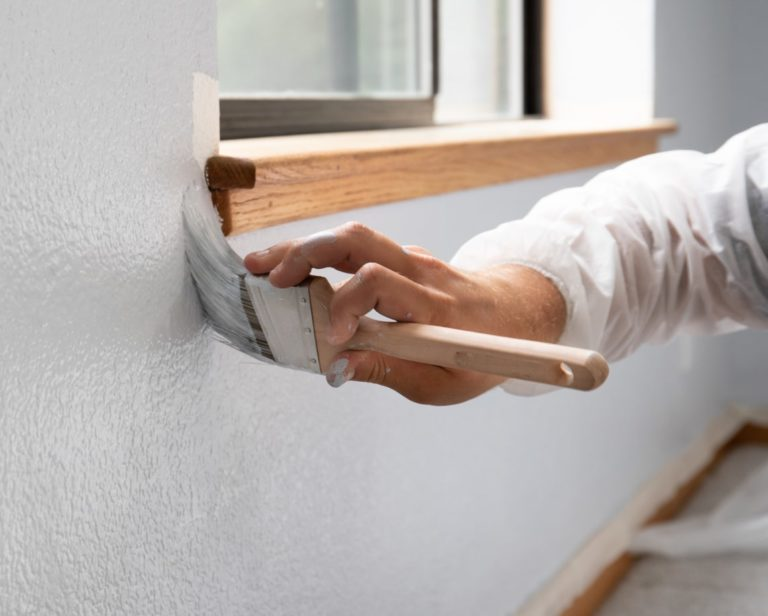 hand-holding-paintbrush-against-wall-near-windowsill-painting-white-paint-colors